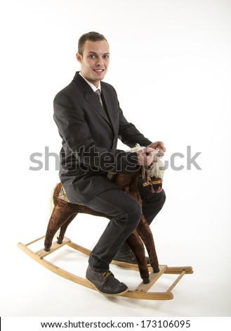 young attractive man on rocking horse - stock photo