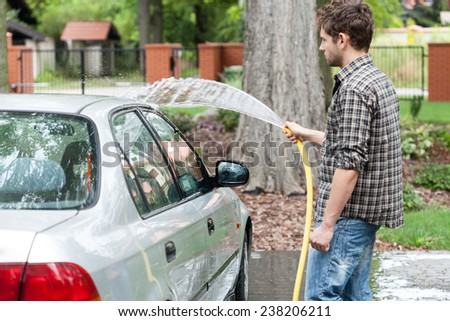 Young attractive man perfusing with water his silver car - stock photo