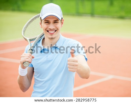 Young attractive man play tennis at court in the morning. - stock photo