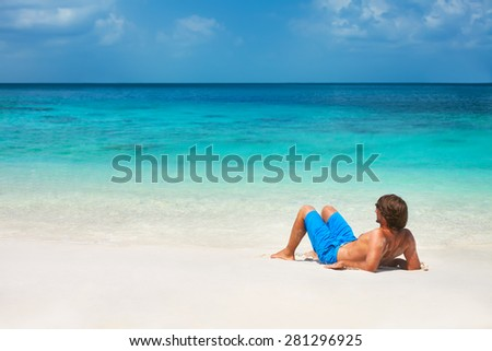 Young attractive man relaxing at the tropical beach - stock photo