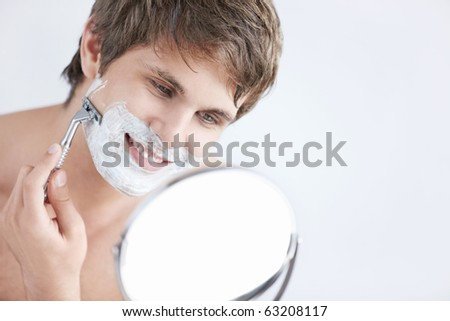 Young attractive man shaves in the mirror - stock photo