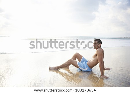 Young attractive man sitting down on the wide shore of a golden sand beach, contemplating the scenery.