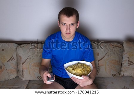 young attractive man sitting in living room and watching tv with chips - stock photo