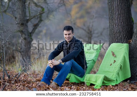 Young attractive man sitting on chair in forest in late november and waiting for someone - stock photo