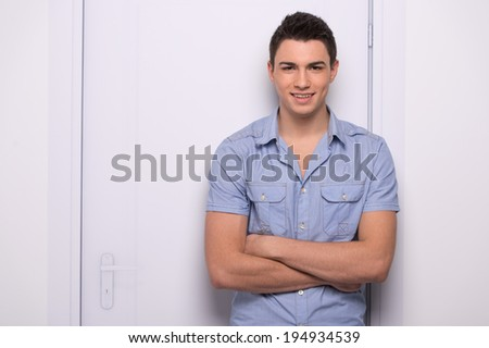 young attractive man standing straight. handsome man leaning against door - stock photo