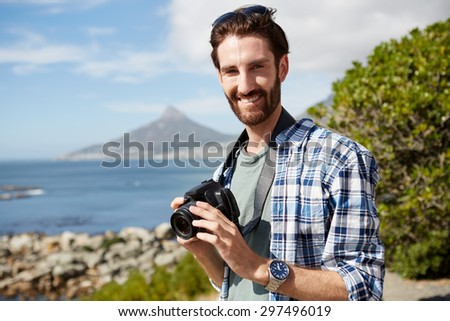 young, attractive man stands near the ocean and poses for a pic with digital camera in his hand