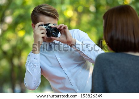young attractive man taking photos of his girlfriend in the park - stock photo