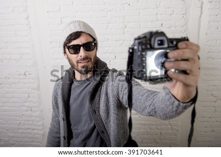 young attractive man wearing casual clothes sunglasses in hipster style modern look holding photo camera shooting self portrait selfie picture or recording video in internet blog and blogger concept - stock photo