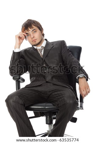 young attractive man with a cigar pensively sitting in an armchair - stock photo