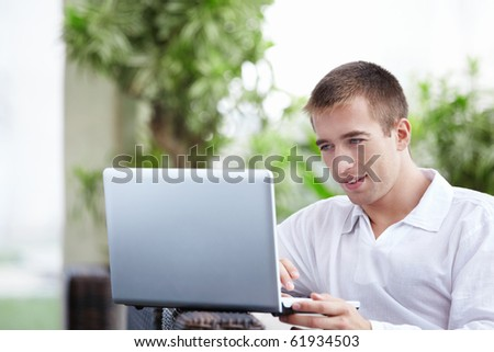 Young attractive man with a laptop in a cafe - stock photo