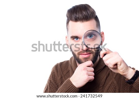 Young attractive man with a magnify glass against white background