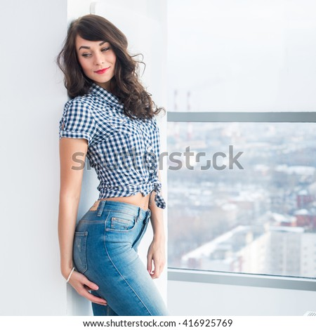 Young attractive model with fit body posing in light studio, wearing jeans and blue checkered shirt, standing sideways. - stock photo