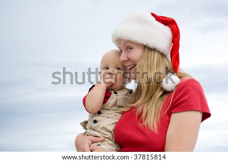 Young attractive mom with Santa's hat and the little baby on the cloudy sky background - stock photo