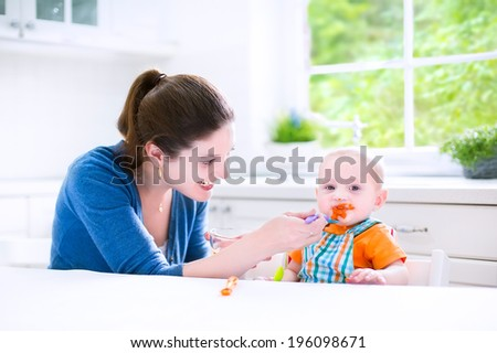 Young attractive mother feeding her cute baby son, giving him his first solid food, healthy vegetable pure from carrot with a plastic spoon sitting in a white sunny kitchen at a window at home - stock photo