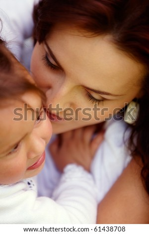 Young attractive mother is kissing her naughty little girl - stock photo