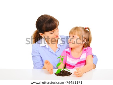 Young attractive mother is telling her daughter about plant - stock photo