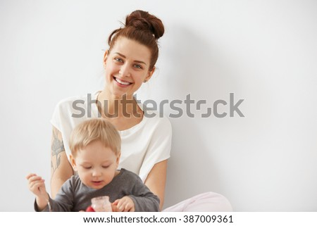 Young attractive mother with her one years old little son dressed in pajamas.  Boy eating a fruit smoothie himself in the bedroom at the weekend together, warm and cozy scene. Selective focus. - stock photo