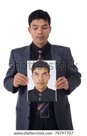 Young attractive nepalese businessman holding its own photo in hands and looking at. Point of conscience. Studio shot. White background. - stock photo