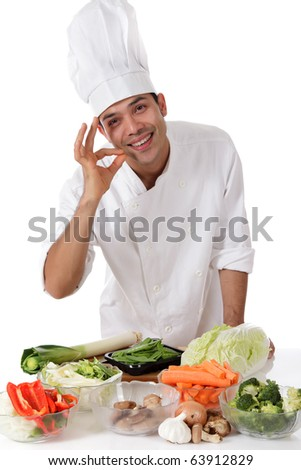 Young attractive nepalese man chef cooking variety of fresh vegetables. Ingredients for oriental food. Studio shot, white background. - stock photo