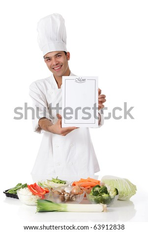 Young attractive nepalese man chef showing the menu list, blank page. Variety of fresh vegetables on table. Studio shot, white background - stock photo