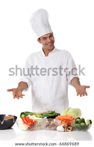 Young attractive nepalese man chef showing variety of fresh vegetables. Ingredients for oriental food. Studio shot, white background. - stock photo