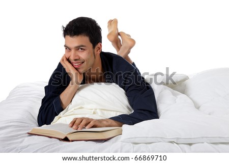 Young attractive nepalese man in pajamas lying prone in  bed and reading a book. Studio shot. White background - stock photo