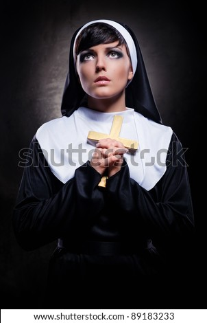 Young attractive nun holding a cross - stock photo