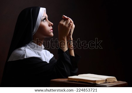 Young attractive nun praying - stock photo