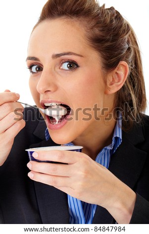 Young attractive office girl eats yogurt during her break, isolated on white - stock photo