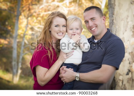 Young Attractive Parents and Child Portrait Outdoors.