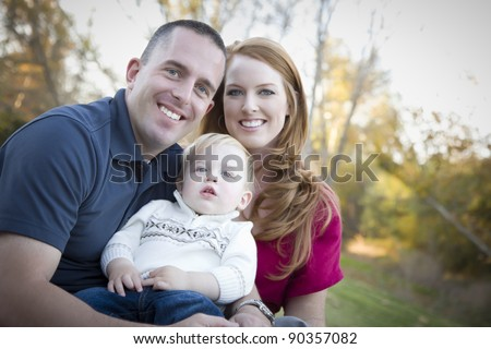 Young Attractive Parents and Child Portrait Outdoors at a Park. - stock photo