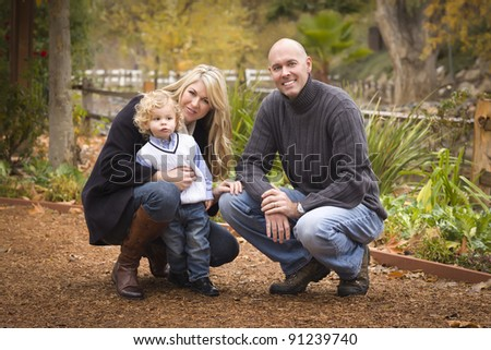 Young Attractive Parents and Child Portrait Outside in the Park.