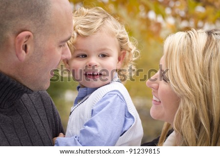 Young Attractive Parents and Child Portrait Outside in the Park. - stock photo