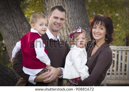 Young Attractive Parents and Children Portrait Outside in the Park. - stock photo