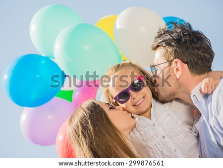 Young attractive parents with balloons kissing their little daughter on the cheek. - stock photo