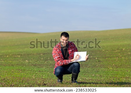 Young attractive peasant monitoring seedlings in the field in autumn - stock photo