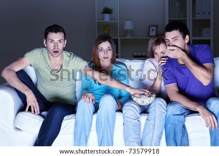 Young attractive people are watching TV at home - stock photo