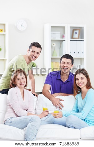 Young attractive people drink juice in the apartment - stock photo