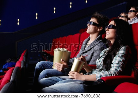 Young attractive people in the cinema - stock photo