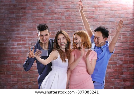 Young attractive people taking selfie with mobile phone on brick wall background