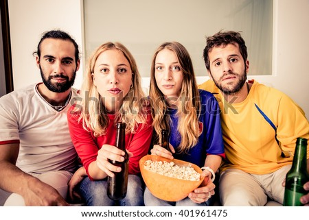 Young attractive people watching TV at home - Group of friends looking at something dramatic on television - stock photo