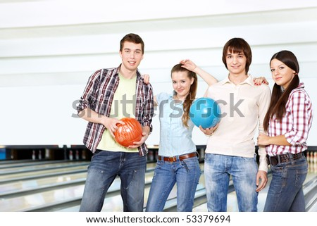 Young attractive people with spheres in bowling - stock photo
