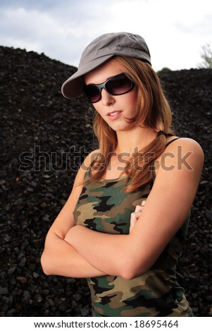 young attractive posing female dressed in camouflage singlet and gray hat - stock photo