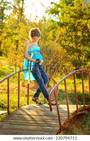 Young attractive pregnant girl with an unusual make-up standing on the bridge at sunny day