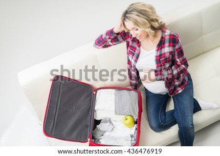 Young attractive pregnant woman packing children's wear to go to maternity clinic. - stock photo