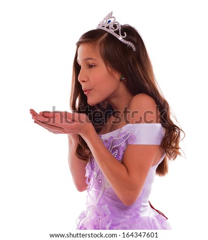 Young Attractive Princess in Cinderella Dress and Crown Blowing Dream from her Hands isolated on white background - stock photo