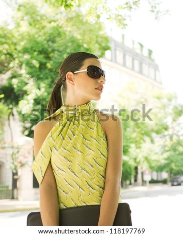 Young attractive professional businesswoman standing in front of a classic office building in a classic city, wearing dark shades. - stock photo