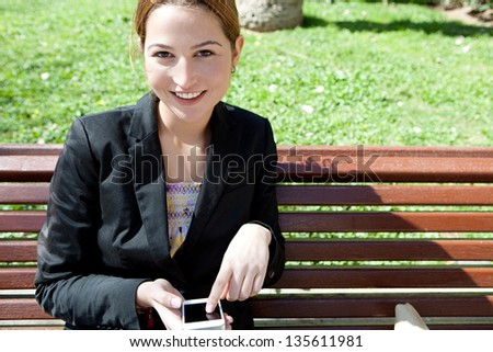 Young attractive professional woman using her smartphone while sitting on a wooden bench in a city park with green grass, smiling at camera.