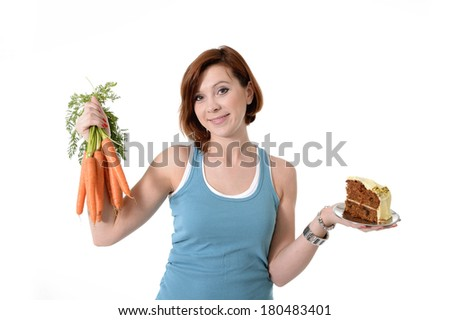 Young Attractive red hair woman in sport clothes  holding carrots and cake in hands in healthy versus tasty junk food in fitness and healthcare nutrition concept isolated on White background - stock photo