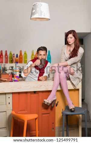 young attractive red haired caucasian girl sitting on the counter with legs and arms crossed with a handsome guy behind the counter drinking coffee, in colorful cafe - stock photo